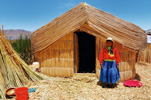 Young local girl on a floating Uros island standing in front of her home